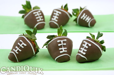 Chocolate covered strawberries decorated like footballs.