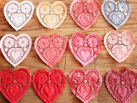 Three rows of different colored, heart-shaped doilies on a wooden table.