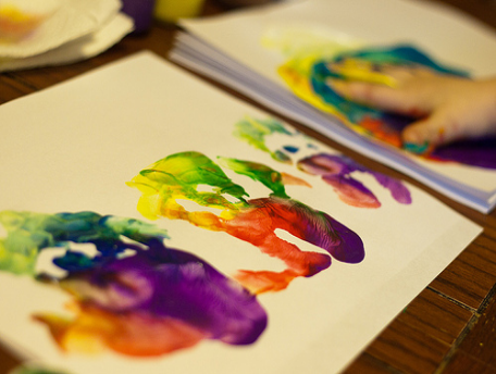 Kids' mutli-colored handprints on a large sheet of paper