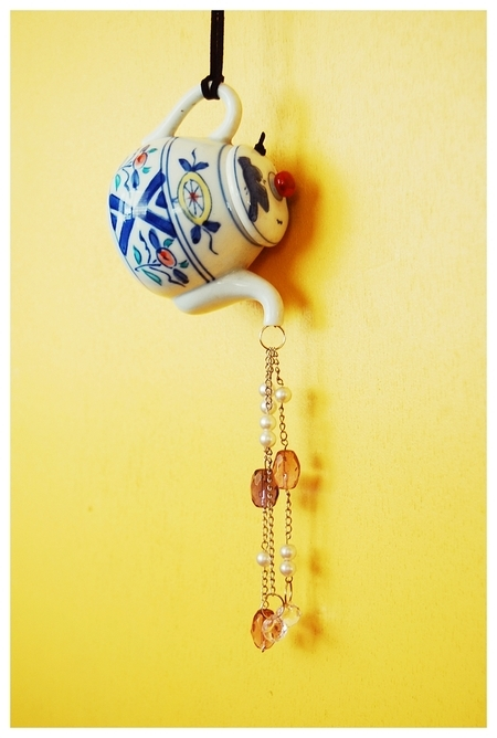 A teapot hung on the wall, with strings of beads emerging from the spout