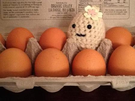 A crochet egg with eyes and a mouth, sitting in an egg carton with real eggs