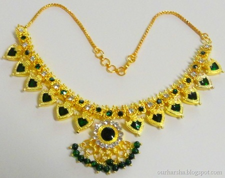 A gold necklace with green jewels
