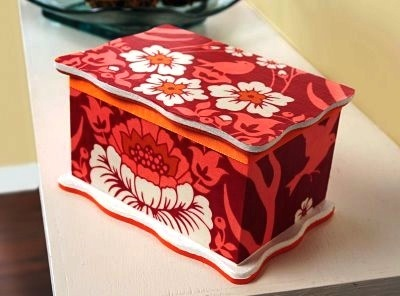 A wooden box decorated with red and pink fabric and paints