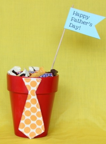 "A small, painted flower pot filled with candy and a ""Happy Father's Day"" flag"