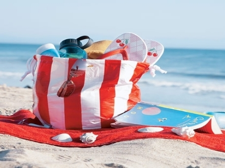 A red and white striped tote bag on the beach