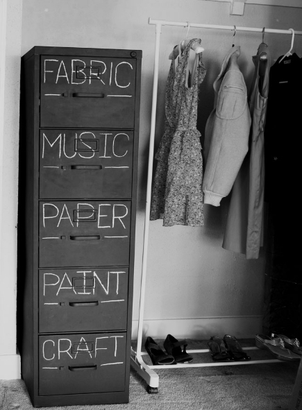 "A filing cabinet painted in black chalkboard paint with words like ""fabric"" and ""music"" written on it"
