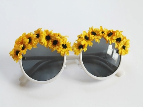 A pair of sunglasses topped with stick-on sunflowers