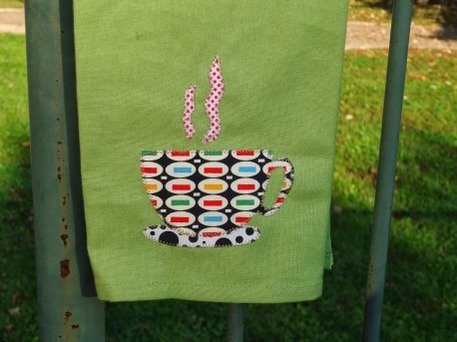 A green hand towel with a tea cup shaped applique