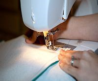 woman sews T-shirts for T-shirt quilt