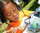 girl paints shoe at craft event