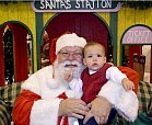 santa claus holds baby at craft fair