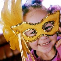 Little girl wearing a hand-made sequined mask.