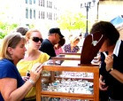 women look at jewelry at craft fair