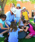 Children gather around a demonstrator at the Folk Arts Fair in Prescott, AZ