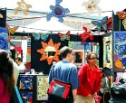 Several shoppers admiring the wares of a booth at the Eco-Urban Union Street Festival