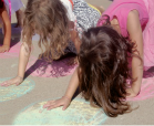 Three little girls playing chalk twister in a driveway