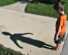 A little boy examining his shadow.