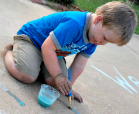 A boy playing with his homemade chalk paint.