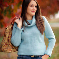 Woman wearing a blue sweater with a cowl neck.