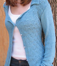 Woman wearing a blue sweater, clasped in front with a small pearl button.