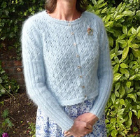 Woman wearing a light blue sweater outdoors.