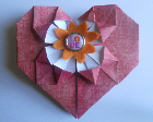 A pink origami heart with an orange button in the center.