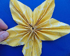 A yellow origami star against a blue background.