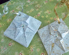 Origami ornaments with ribbons attached against a green background.
