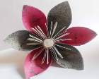 Origami flower with pink and grey petals and a button embellishment in the middle.