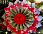 Star-shaped ornament with layers of paper and a button in the middle.