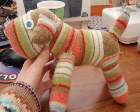 A stuffed dog made out of striped socks.