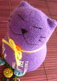 Stuffed cat made from a purple sock, with a yellow ribbon around its neck.
