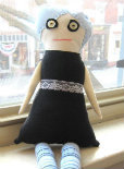 A zombie doll wearing a black dress and with button eyes.