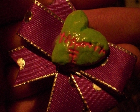 A red hair bow with a zombie green heart in the middle.