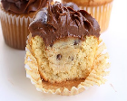 Yellow cupcake with chocolate frosting and stuffed with cookie dough.