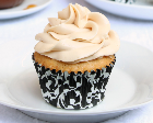 Yellow cupcake with white frosting, in a black and white cupcake paper.