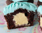 Chocolate cupcake stuffed with ice cream, with blue frosting on top.
