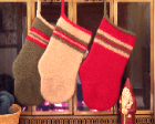 Three DIY stockings made of wool, one red, one white, and one green.