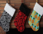Three homemade stockings with wild patterned fabric and a soft cuff at the top.