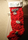 A long, red DIY stocking made from granny squares knitted together.