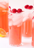 Pink liquid with berries floating on top in tall, thin glasses