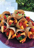 Chunks of fresh fruit in waffle cones.