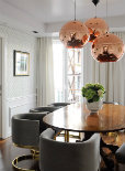 A kitchen with fashionable lights hanging over the dining table
