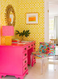 Brightly decorated room with a pink dresser and yellow wallpaper