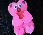 A bear made of pink, foam hearts.