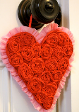 A heart covered in crepe paper rosettes hung on a doorknob.