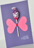 A card made of purple paper with a lollipop stuck to the front.