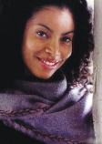 African-American woman wearing a blue, wool scarf with embroidered vines on the edge.
