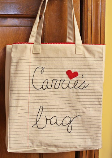 Canvas bag with lines like looseleaf paper and words embroidered on it