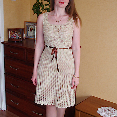 A cream, crochet dress with a ribbon at the waist.